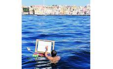 Cristini dipinge Procida nuotando