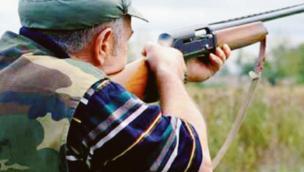 Cacciatore entra in cortile per sparare a una gallina